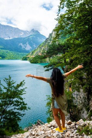 Photo for Back view of woman standing with open arms near Piva Lake (Pivsko Jezero) in Montenegro - Royalty Free Image