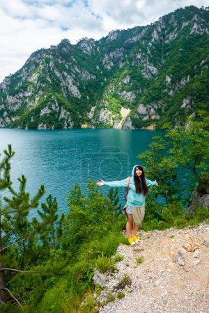 beautiful woman standing with open arms near Piva Lake (Pivsko Jezero) in Montenegro