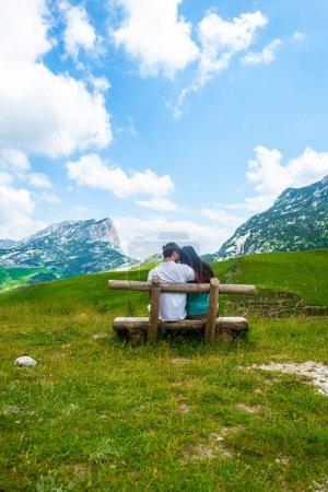 Photo pour Vue arrière du couple assis sur un banc en bois et regardant les montagnes dans le massif de Durmitor, Monténégro - image libre de droit