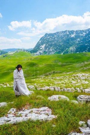 Photo pour Jolie femme en couverture debout sur la vallée verte dans le massif de Durmitor, Monténégro - image libre de droit