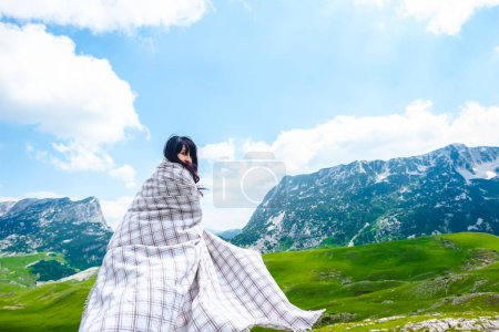 Photo for Beautiful woman in blanket walking on valley near mountains in Durmitor massif, Montenegro - Royalty Free Image