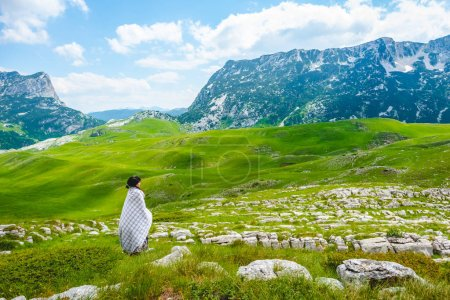 woman in blanket looking at valley in Durmitor massif, Montenegro