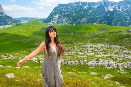 Foto de Atractiva mujer de pie con ojos cerrados y brazos abiertos en el valle en el macizo de Durmitor, Montenegro - Imagen libre de derechos