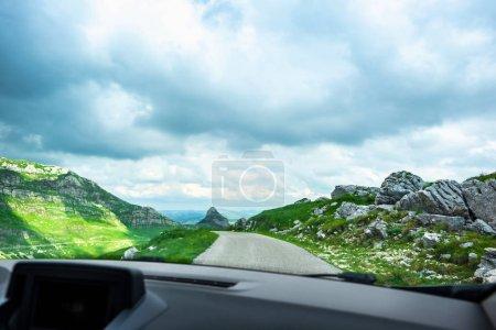 Photo pour Voiture sur route de montagne avec ciel nuageux dans le massif de Durmitor, Monténégro - image libre de droit