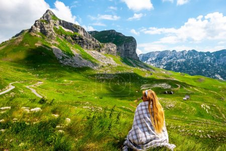 back view of woman in blanket looking at mountains in Durmitor massif, Montenegro