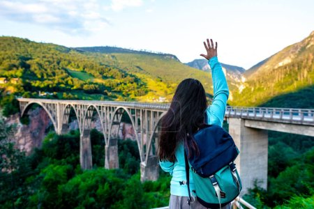 back view of woman waving hand to concrete arch bridge in Montenegro