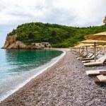 Sun loungers on empty beach of adriatic sea in Bud...