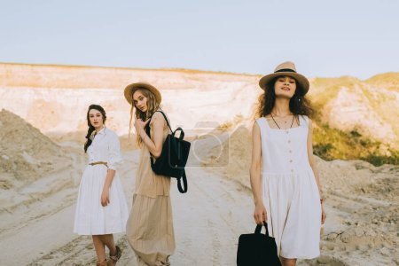 pretty girls in elegant dresses and straw hats walking with backpacks in sandy canyon