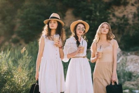 Photo pour Belles filles dans des chapeaux de paille élégantes tenue café latte - image libre de droit