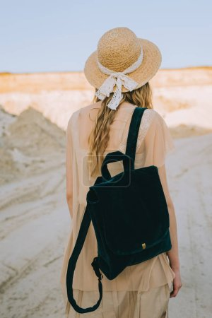 back view of girl in straw hat walking with backpack in sandy canyon