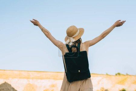 Photo pour Vue arrière du jeune fille au chapeau de paille avec commandes de sac à dos avec une main tendue dans le canyon de sable - image libre de droit