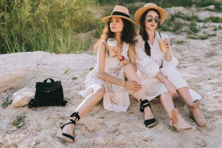 Photo pour Jolies filles dans des chapeaux de paille avec café latte, assis sur le sol - image libre de droit