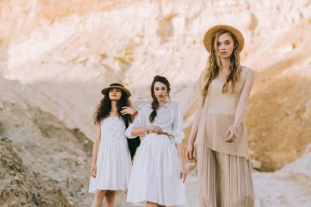 beautiful young women in elegant dresses and straw hats posing in sandy canyon