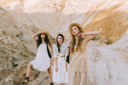 pretty girls in trendy dresses and straw hats posing in sandy canyon