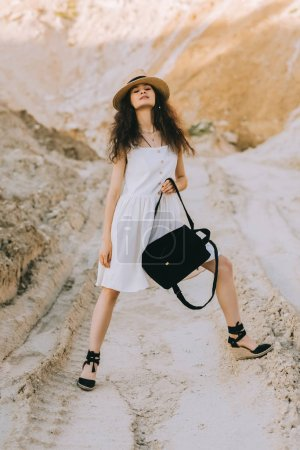 charming girl in stylish dress posing with backpack in sandy canyon