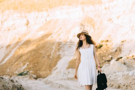 Photo for Beautiful stylish girl in straw hat walking with backpack in sandy canyon - Royalty Free Image