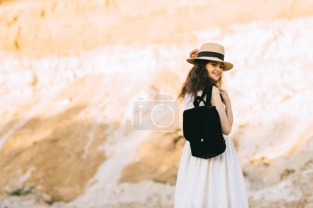 Photo for Beautiful smiling girl in straw with backpack in sandy canyon - Royalty Free Image