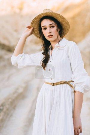 attraktives stilvolles Mädchen mit Strohhut posiert in sandiger Schlucht