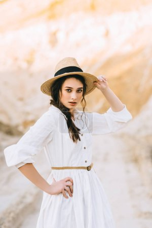 attractive girl posing in elegant dress and straw hat in sandy canyon