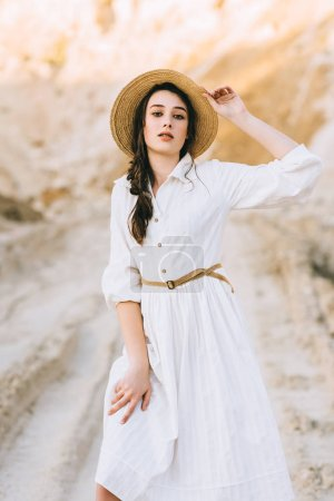 charming stylish girl posing in white dress and straw hat in sandy canyon