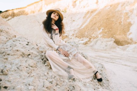 Photo pour Femme élégante qui pose en mode robe et chapeau de paille en sable canyon - image libre de droit