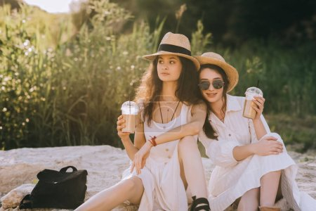 pretty girls in elegant dresses with cups of coffee latte sitting on ground