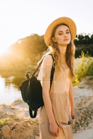 attractive stylish girl in trendy dress posing with black backpack near lake with backlit