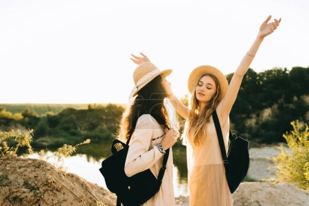 beautiful female friends in straw hats with backpacks having fun near lake with back light