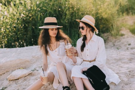 attractive girlfriends in straw hats with cups of coffee latte sitting on ground