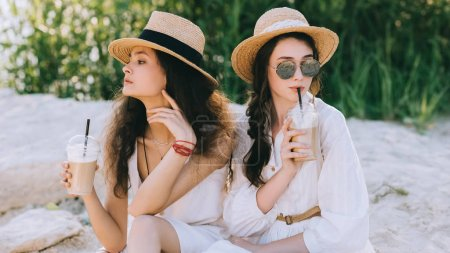 beautiful female friends in straw hats drinking coffee latte and sitting on ground