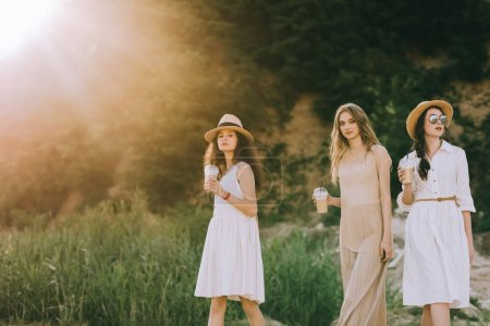 Foto de Charming girls in straw hats holding coffee latte and walking in nature with back light - Imagen libre de derechos