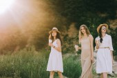 charming girls in straw hats holding coffee latte and walking in nature with back light