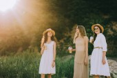beautiful female friends in straw hats walking in nature with plastic cups of coffee latte