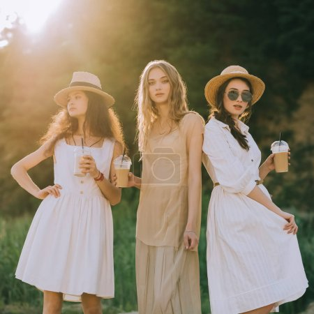attractive stylish girls in straw hats holding coffee latte posing, with sunlight