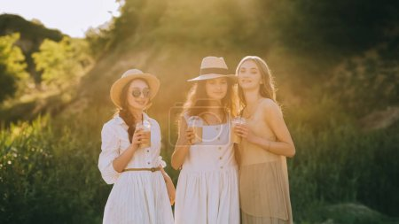 elegant stylish girlfriends in straw hats holding cups with coffee latte and posing, with sunlight