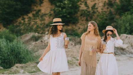 Photo pour Belles filles dans des chapeaux de paille marcher dans la nature avec des tasses en plastique du café latte - image libre de droit