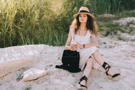 attractive curly girl with coffee latte and backpack sitting on ground
