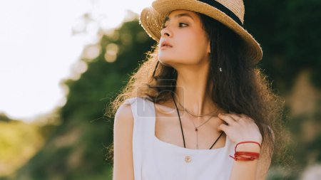 elegant curly girl posing in white dress and straw hat