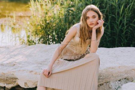 attractive elegant girl in dress sitting on ground near pond
