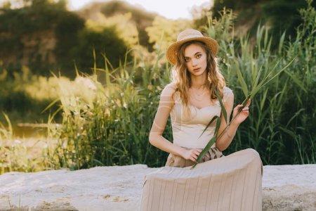 elegant stylish girl in straw hat sitting on ground near pond
