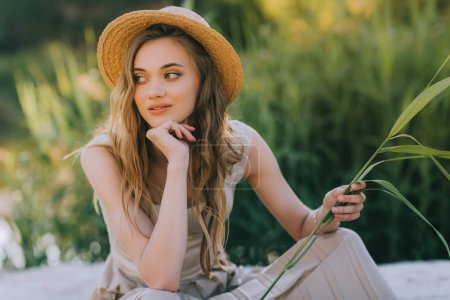 beautiful happy girl in elegant dress and straw hat sitting on ground