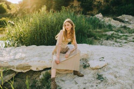 beautiful blonde girl in trendy dress sitting on ground