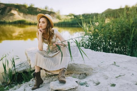 elegant blonde girl in stylish straw hat sitting on ground near lake