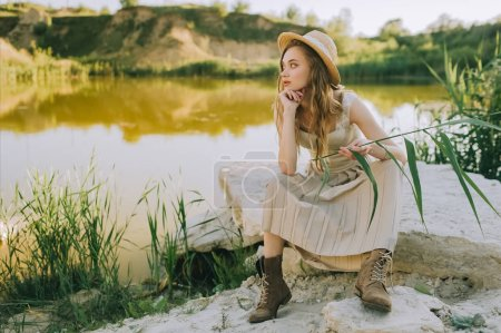 stylish girl in elegant dress and straw hat sitting on ground near pond