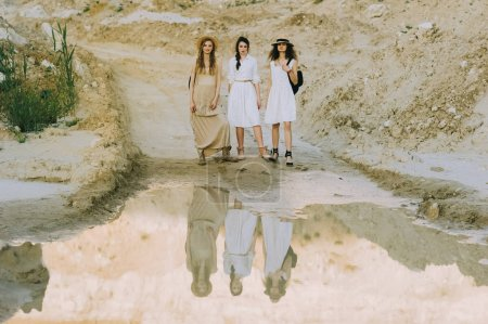 elegant stylish girls posing near big puddle in sandy canyon