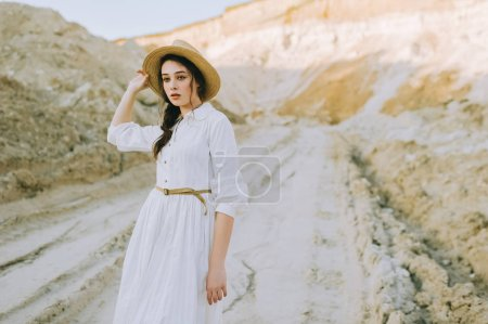 Photo for Attractive young woman in white dress and straw hat posing in sandy canyon - Royalty Free Image