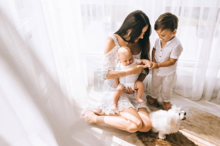 high angle view of beautiful happy mother sitting on floor with kids and bichon dog