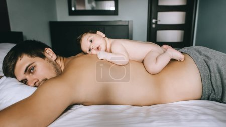 adorable infant boy laying on father back in bed at home