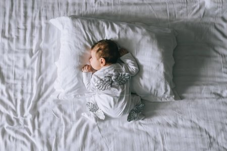 overhead view of little baby boy in costume with wings laying in bed at home