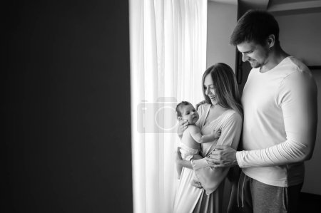 black and white picture of happy family carrying little baby boy in front of curtains at home